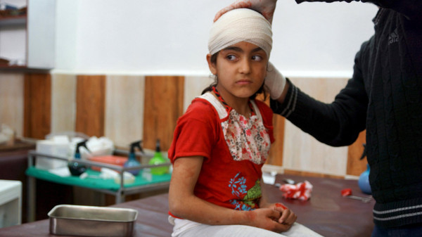 A medic wraps a bandage around an injured girl's head after what activists said were airstrikes by warplanes loyal to Syria's President Bashar al-Assad in Da'el town, north of Daraa, April 19, 2015.