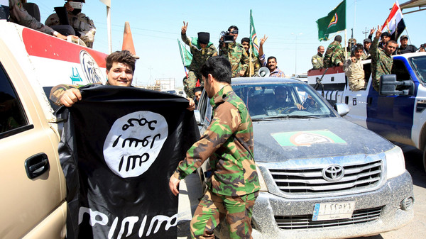 Paramilitary fighters hold an ISIS flag which they pulled down during victory celebrations after returning from Tikrit in Kerbala.