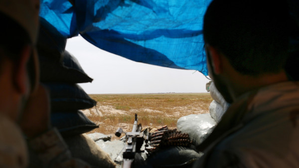 In this Monday, April 20, 2015 photo, two Sunni fighters overlook an ISIS group-held village on the other side of the frontline in northern Iraq.