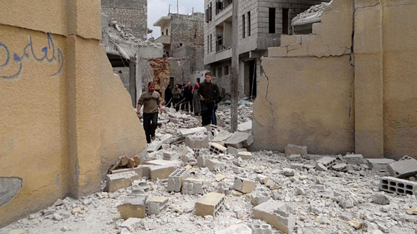 This photo posted by the anti-government activist website of the Syrian Observatory for Human Rights shows Syrians walking at the damaged backyard of a school after an airstrike in Aleppo.