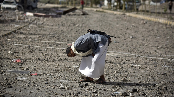 A Shiite fighter known as Houthi checks an item on a street littered by debris after a Saudi-led airstrike hit a site where many believe the largest weapons cache in Yemen's capital, Sanaa, is located.