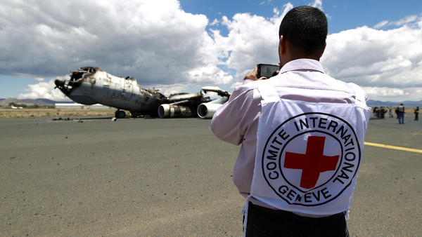 A member of the International Committee of the Red Cross takes pictures of the wreckage of a Yemeni air force military transport aircraft on the tarmac of the rebel-controlled international airport of Sanaa on May 5, 2015.