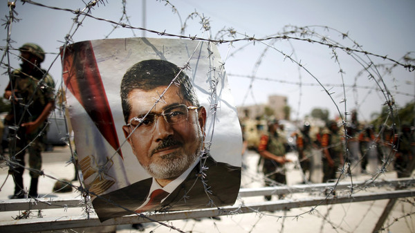 A portrait of deposed Egyptian President Mohamed Mursi is seen on barbed wire outside the Republican Guard headquarters in Cairo.