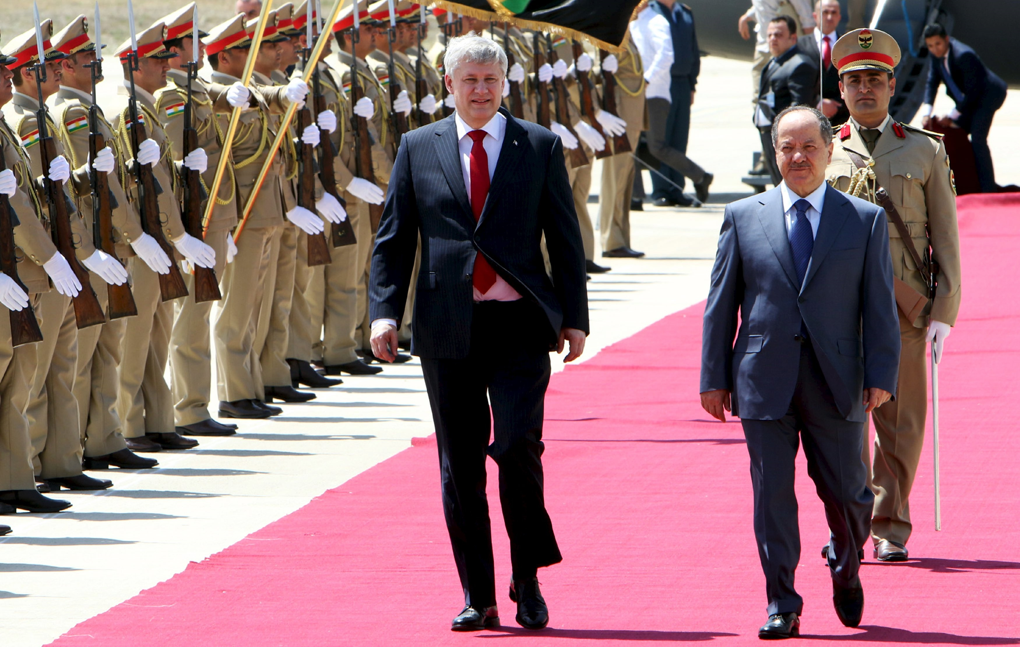 Canada's Prime Minister Harper and Iraq's Kurdish regional President Barzani walk during a welcoming ceremony after arriving at the airport in Erbil.