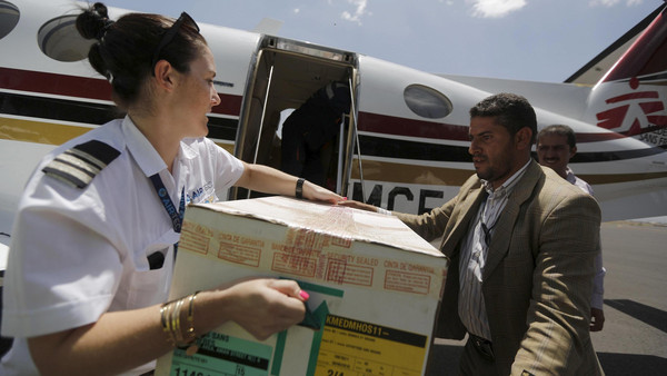 Pilot helps unload aid package from a Doctors Without Borders plane at Sanaa International Airport.
