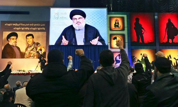 Hezbollah supporters listen to the organization's leader.