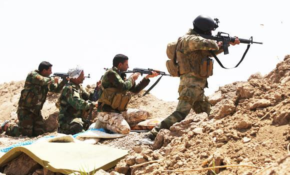Iraqi soldiers and Shiite fighters from the popular committees hold a post as they fire towards Islamic State (IS) group positions in the Garma district of Anbar province west of the Iraqi capital Baghdad, on Tuesday.