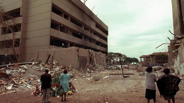 This August 7, 1998, file image shows Kenyan residents looking at the US embassy (L) days after the bomb blast that killed 224 people in the East African nation.