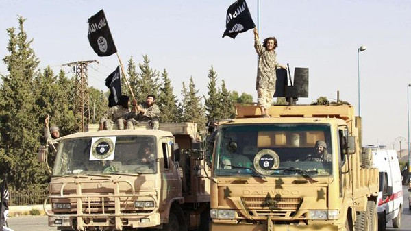 Militant Islamist fighters wave flags as they take part in a military parade in Syria's northern Raqqa province June 30, 2014.