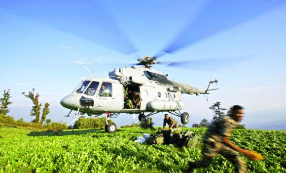 Nepalese army personnel jump out from an Indian helicopter as they unload earthquake relief aid on a hilltop at Dolkha district, Nepal on Thursday.