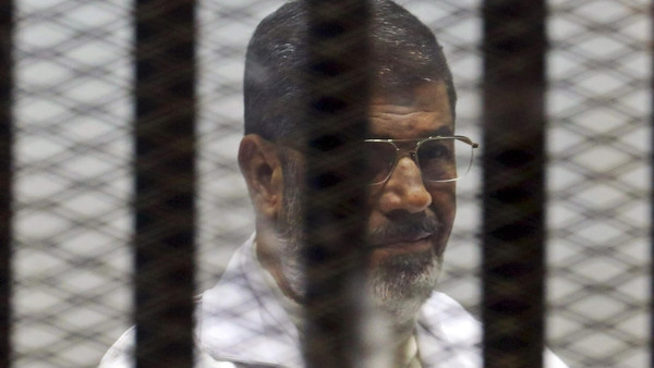 Ousted Egyptian President Mohamed Mursi sits behind bars with other Muslim Brotherhood members at a court in the outskirts of Cairo, December 29, 2014.