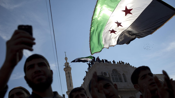 Men hold revolutionary Syrian flags during an anti-government protest in a town in northern Syria.