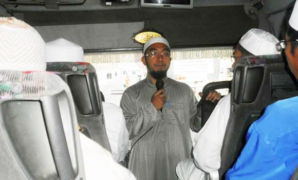 A mutawwif on a bus briefs Umrah pilgrims on religious rites.