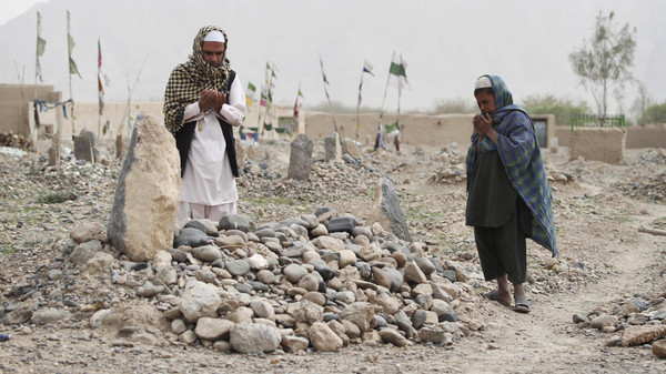 Afghan villagers pray over the grave of one of the sixteen victims killed in a shooting rampage in the Panjwai district of Kandahar province south of Kabul, Afghanistan, Saturday, March 24, 2012.