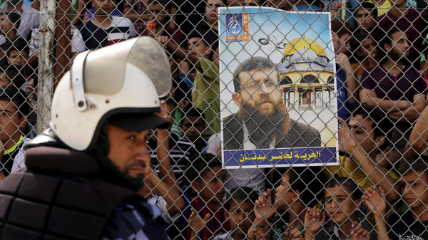 Palestinian policeman loyal to Hamas stands guard as spectators stand behind a fence and hold a poster depicting Palestinian prisoner Adnan.