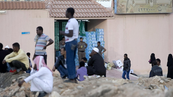 In this Wednesday, Nov. 13, 2013 file photo, Saudi security forces watch Ethiopians gather as they wait to be repatriated in Manfouha, southern Riyadh.
