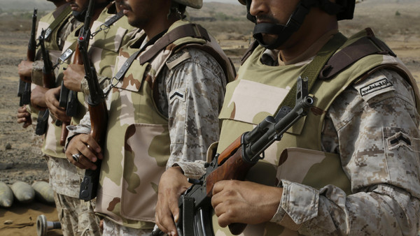 Saudi soldiers with their weapons stand guard at the Yemen border in Jizan, Saudi Arabia.