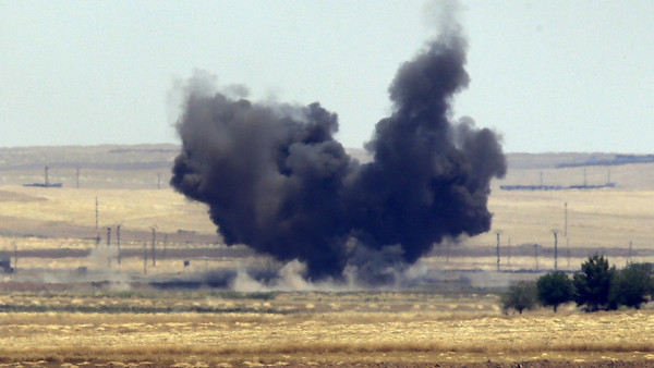 The Turkish side of the border between Turkey and Syria, in Akcakale, Sanliurfa province, southeastern Turkey, smoke from a US-led airstrike rises over the outskirts of Tal Abyad, Syria, Sunday, June 14, 2015.