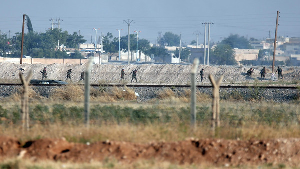 The Turkish side of the border between Turkey and Syria, in Akcakale, southeastern Turkey, Kurdish fighters advance in the outskirts of Tal Abyad, Syria.