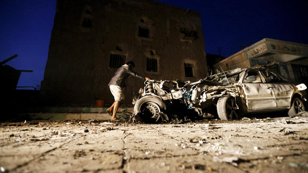 A man checks the wreckage of a car at the site of a car bomb attack in Yemen's catpital Sanaa June 17, 2015.