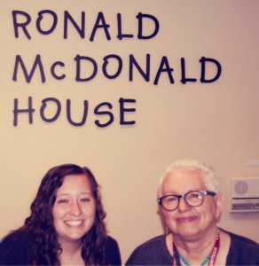 Volunteers smile under our House sign