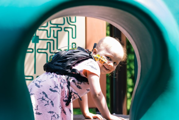 Ireland Wylam smiles at the camera on a play structure at the Seattle House