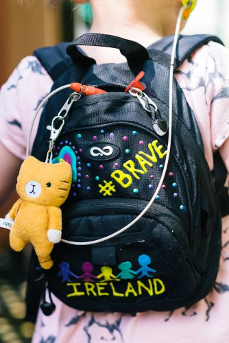 Ireland's backpack, which is adorned with #Brave and #Strong