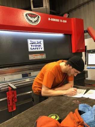 SMF employee writing on table in front of an RMT machine