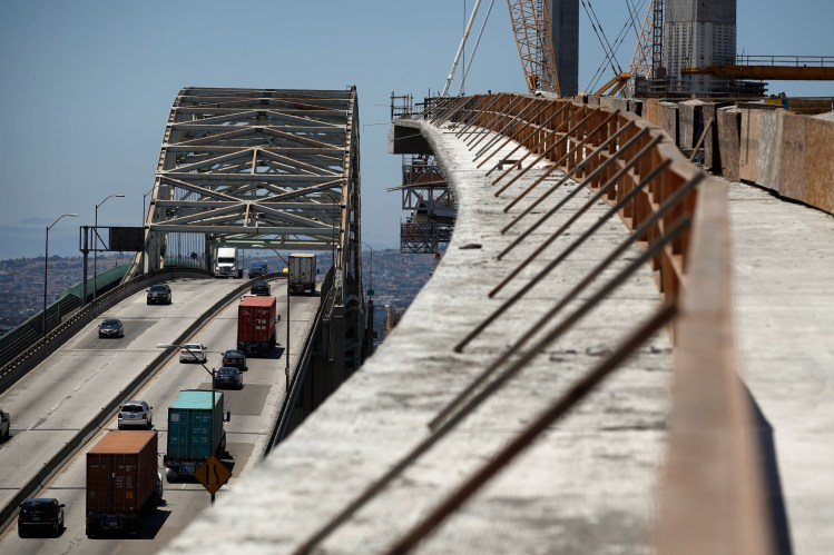 FILE - Traffic moves on the old Gerald Desmond Bridge next to its replacement bridge under construction in Long Beach, Calif., July 2, 2018. President Donald Trump's tariffs provoke retaliatory tariffs on U.S. exports.