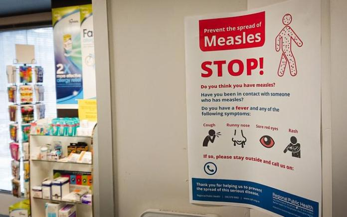 A poster at a medical center warns against the spread of measles.