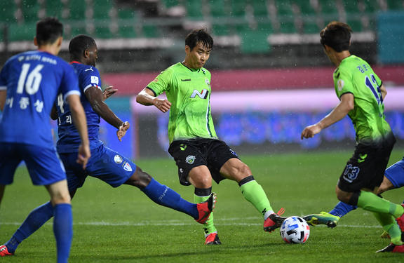 Jeonbuk Hyundai Motors' Lee Dong-gook (C) dribbles the ball against Suwon Samsung Bluewings during the opening game of South Korea's K-League football match at Jeonju World Cup Stadium in Jeonju on May 8, 2020.