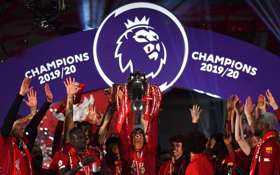 Liverpool's Brazilian midfielder Roberto Firmino (C) lifts the Premier League trophy during the presentation following the English Premier League football match between Liverpool and Chelsea at Anfield in Liverpool, north west England on July 22, 2020.