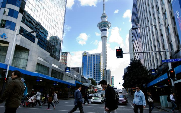 AUCKLAND, NZ - MAY 29:Traffic on Queen street with the Skytower in the background on May 29 2013.It's a major commercial thoroughfare in the Auckland CBD, New Zealand's main population center.