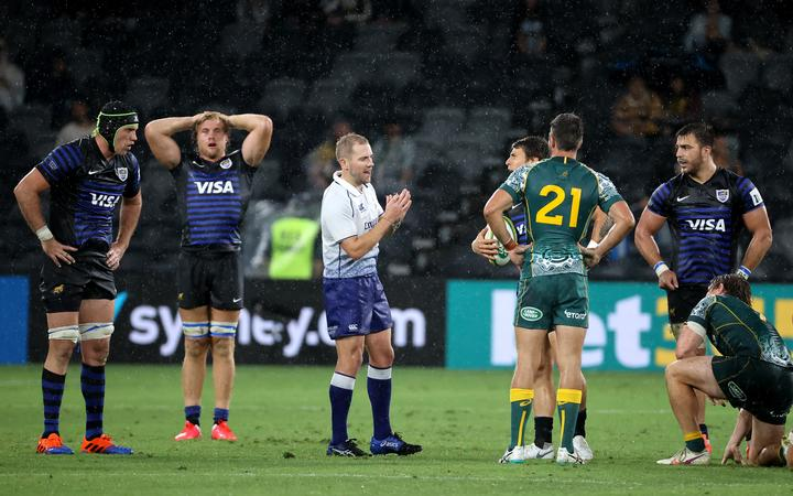 Australian and Argentinian players react as referee Wayne Barnes (C) blows the final whistle during the 2020 Tri-Nations rugby match between the Australia and Argentina in Sydney on December 5, 2020. (
