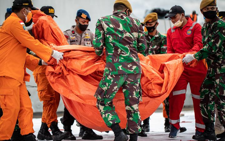 Rescue personnel moving bodies and debris recovered from the crash site of Sriwijaya Air flight SJ182 at the port in Jakarta on January 10, 2021.