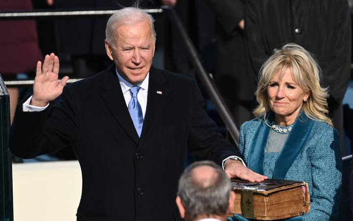 Joe Biden (L), flanked by incoming US First Lady Jill Biden is sworn in as the 46th US President by Supreme Court Chief Justice John Roberts on January 20, 2021, at the US Capitol in Washington, DC.