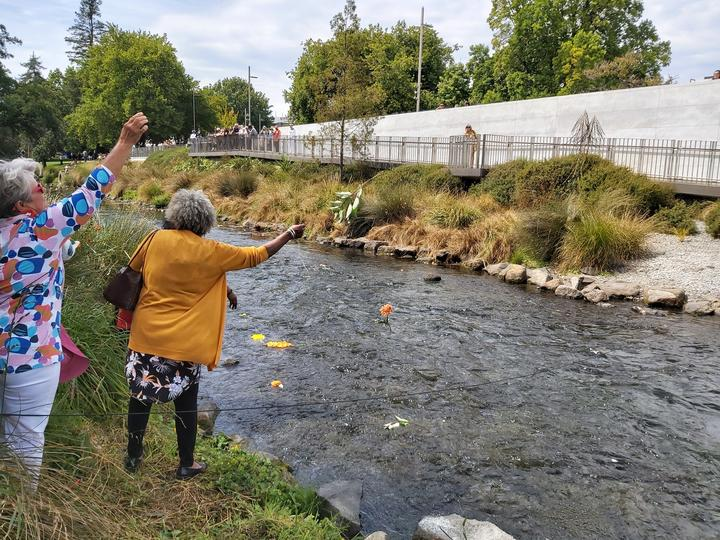 People throw flowers into the River of Flowers.