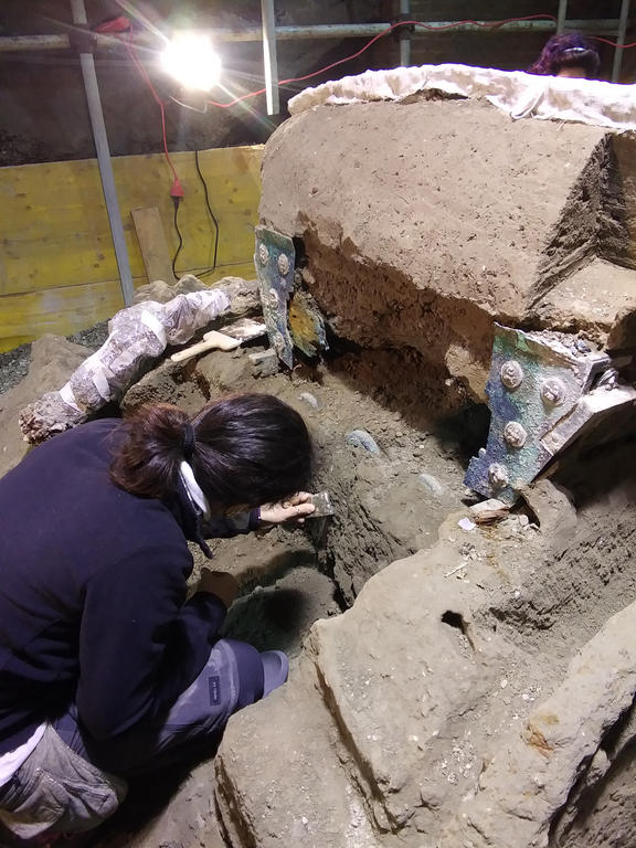 An archaeologist working at the site where a large Roman four-wheeled ceremonial chariot was discovered near the The archaeological park of Pompeii.