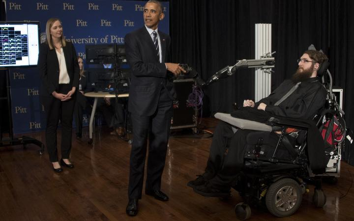 US President Barack Obama (C) speaks with neuro interface patient Nathan Copeland (R) as he tours innovation projects at the White House Frontiers Conference at the University of Pittsburg in Pittsburg, Pennsylvania, on October 13, 2016.