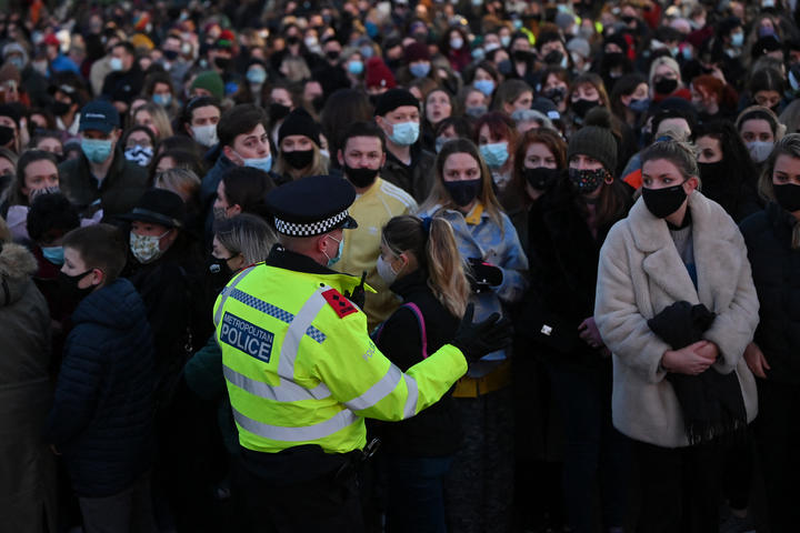 A police officer asks well-wishers not to linger and to move on as they gather at the band-stand where a planned vigil in honour of murder victim Sarah Everard, which was officially cancelled due to Covid-19 restrictions, was to take place on Clapham Common, south London on 13 March 2021.