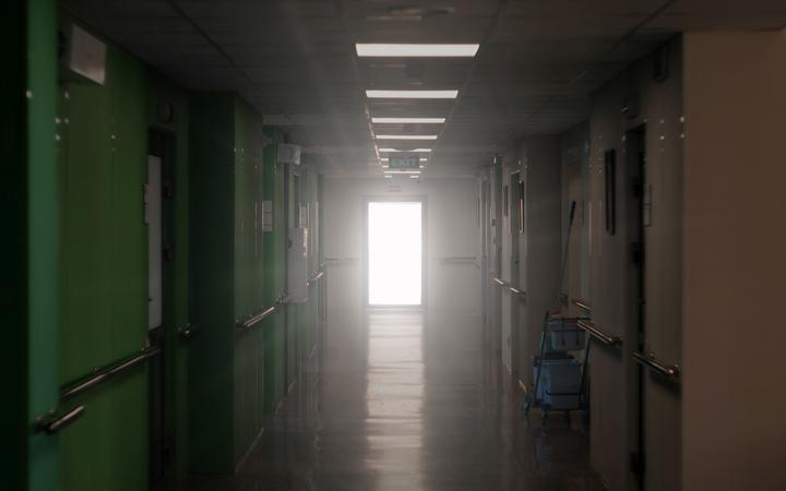 blurred dark hospital corridor with a luminous door at its end - an allegory of clinical death