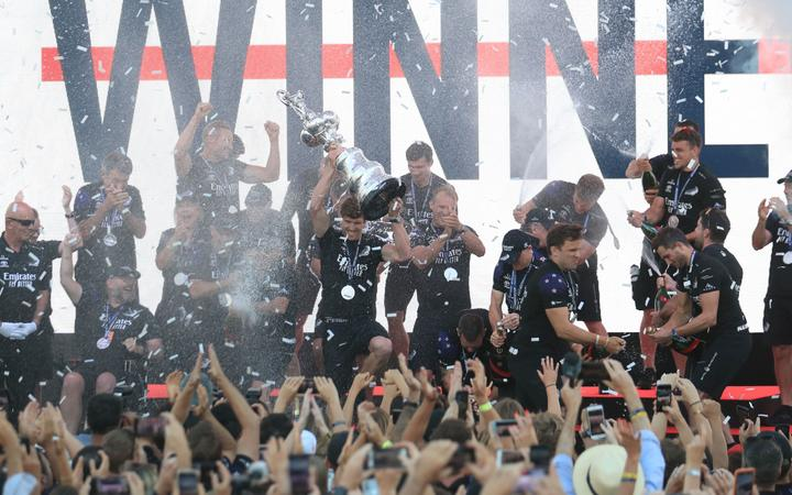 Team New Zealand's skipper Peter Burling (C) holds the America's Cup, affectionately known as the Auld Mug, after winning the 36th America's Cup against Luna Rossa Prada in Auckland on March 17, 2021.