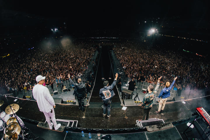 Six60 waving to fans from the stage at Eden Park.
