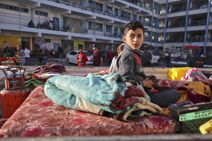 A Palestinian boy who fled his home due to Israeli air and artillery strikes sits on a mattress at a school hosting refugees in Gaza city yesterday.