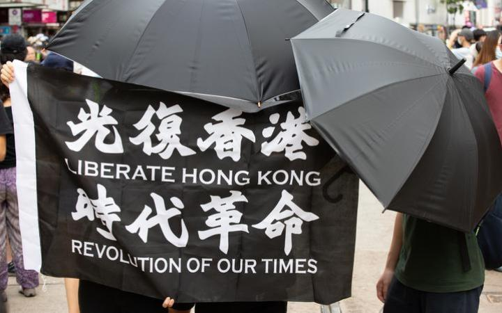 "Protesters hold a ""Liberate Hong Kong, Revolution of our times"" flag while covering their face due to the now introduced National Security Law in Hong Kong, China, on July 1, 2020."