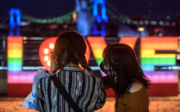 People wearing face masks take pictures at Odaiba area of Tokyo during the evening hour on July 12, 2020. (Photo by Philip FONG / AFP)