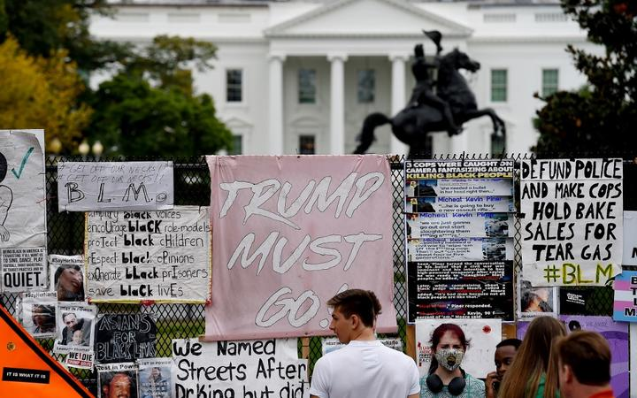 People stand at Black Lives Matter Plaza in Washington, DC, on October 10, 2020, ahead of a speech by US President Donald Trump at the White House.
