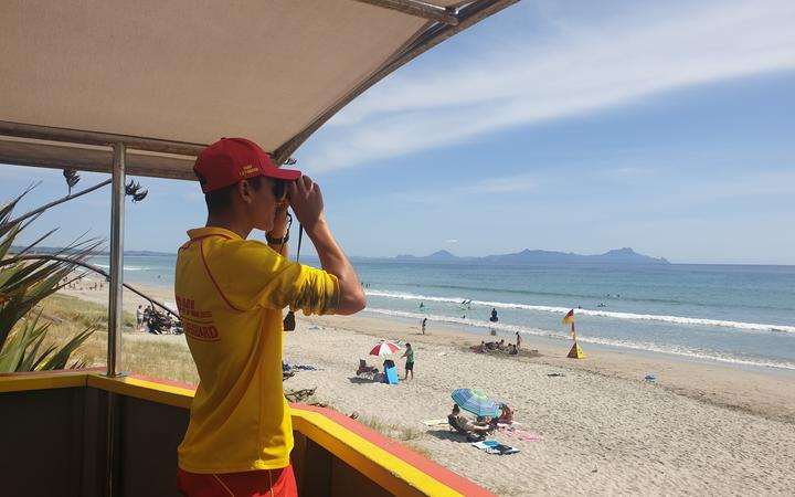 SLSNZ volunteer Surf Lifeguard with binoculars