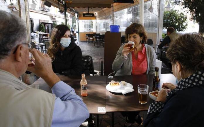 People in a restaurant in Granada on October 23, 2020. COVID-19 infections are increasing in Granada (Spain) and the government of Andalusia has decided to make it compulsory to wear face masks