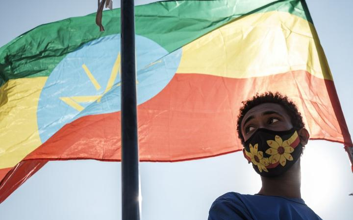 A youngster stands below an Ethiopian national flag during a blood donation rally organised by the city administration of Addis Ababa on 12 November, 2020.